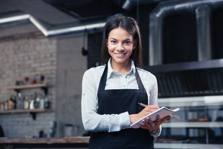 Happy charming female waiter in apron writing order and looking at camera
