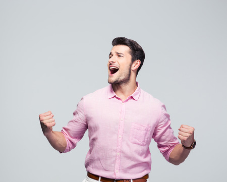 Young businessman celebrating his success over gray background