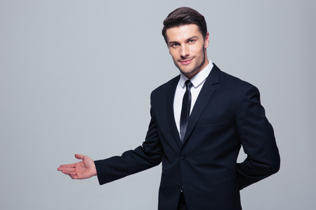 Foto de Businessman with arm out in a welcoming gesture over gray background - Imagen libre de derechos
