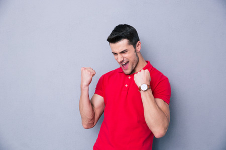 Photo for Casual man celebrating success over gray background - Royalty Free Image