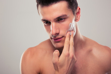 Photo pour Handsome man applying facial cream over gray background - image libre de droit