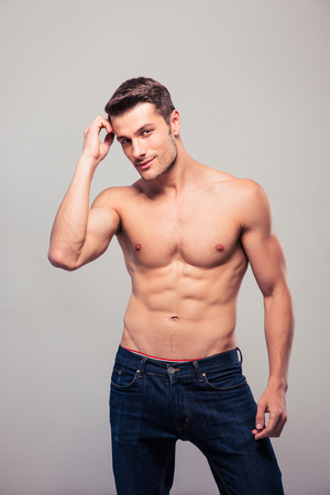 Sexy young man in jeans posing over gray background and looking at camera