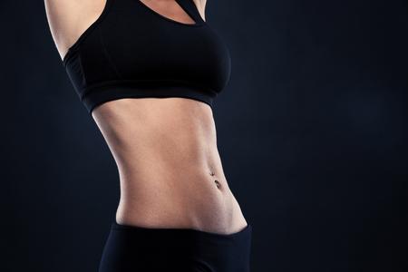 Foto de Closeup of a fit woman's abs isolated over black background - Imagen libre de derechos
