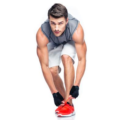 Foto de Fitness man tie shoelaces isolated on a white background. Looking at camera - Imagen libre de derechos