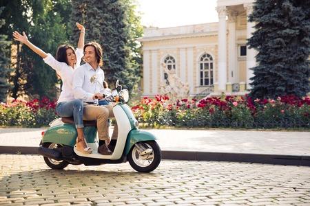 Foto de Happy young couple traveling in scooter in old european city - Imagen libre de derechos