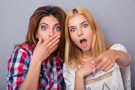 Portrait of a two surprised women standing over gray background and looking at cameraの写真素材