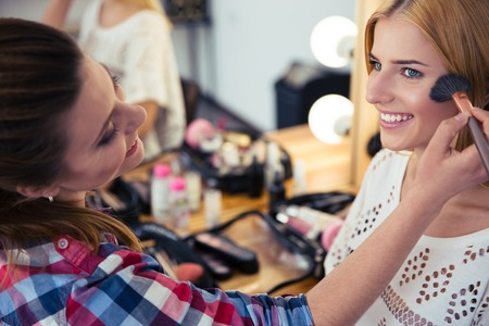 Young woman applying makeup to model in salonの写真素材
