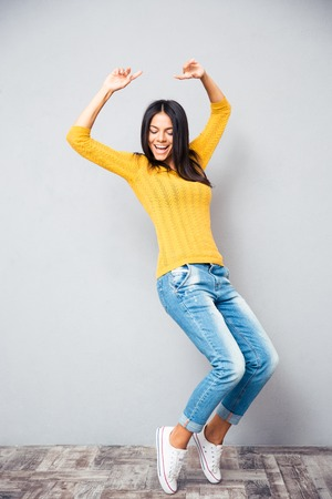 Portrait of a happy young woman dancing on gray background