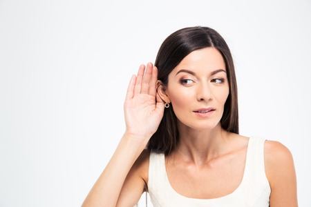 Beautiful woman puts a hand to the ear to hear better isolated on a white background