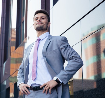 Portrait of a happy confident businessman in suit standing outdoors
