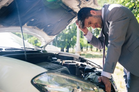 Man in suit looking under the hood of breakdown car outdoors