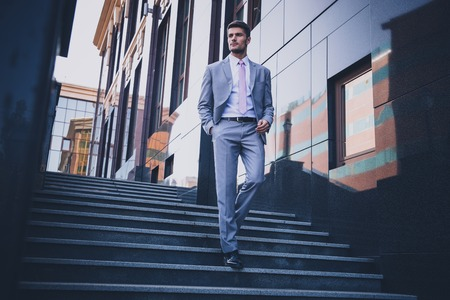 Photo pour Full length portrait of a handsome thoughtful businessman walking on the stairs outdoors - image libre de droit