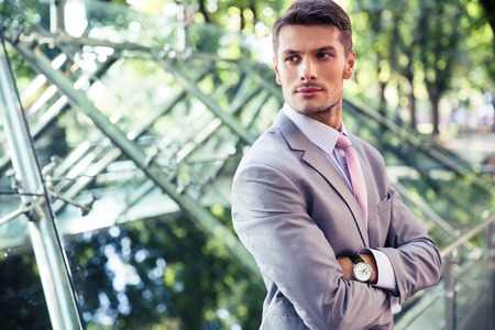 Portrait of a confident businessman standing with arms folded outdoors near glass building
