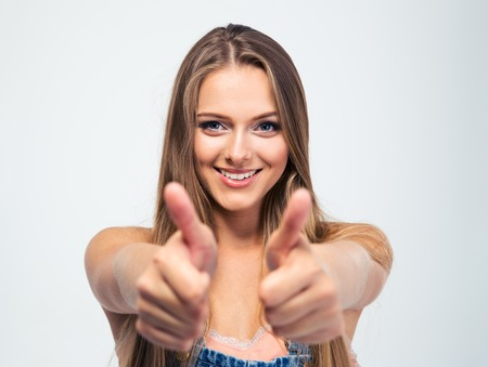 Smiling young girl showing thumbs up isolated on a white background