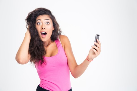 Shocked young woman standing with smartphone and looking at camera isolated on a white background