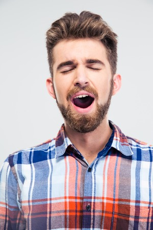 Portrait of a young man singing with closed eyes isolated on a white background