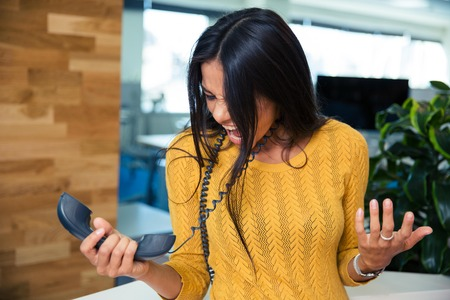 Angry businesswoman screaming on phone in office