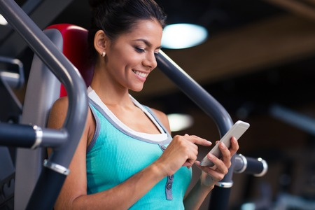 Foto de Portrait of a cheerful sports woman using smartphone in fitness gym - Imagen libre de derechos