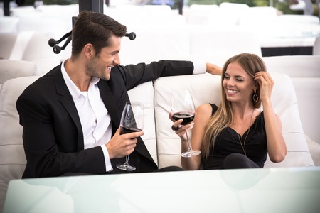 Photo pour Happy elegant couple drinking red wine in restaurant - image libre de droit