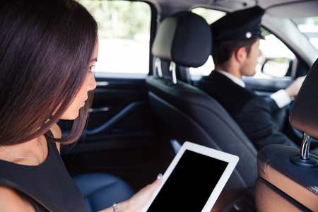 Woman using tablet computer while riding in taxi