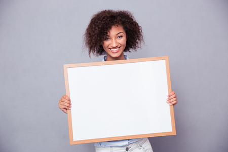 Portrait of a smiling afro american woman holding blank board over gray background