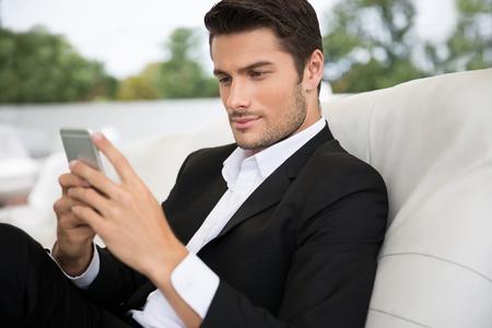 Photo pour Portrait of a handsome man using smartphone outdoors in restaurant - image libre de droit