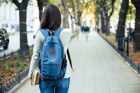 Back view portrait of a female student walking in the city park outdoorsの写真素材
