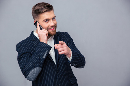 Portrait of a smiling businessman talking on the phone and pointing finger at camera over gray background