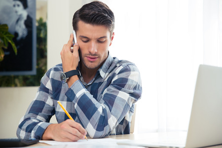 Photo for Portrait of a man making notes on the bills while talking on the phone at home - Royalty Free Image