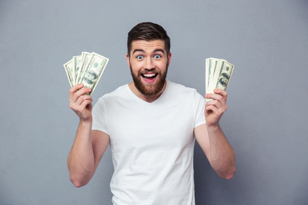 Portrait of a cheerful man holding dollar bills over gray background