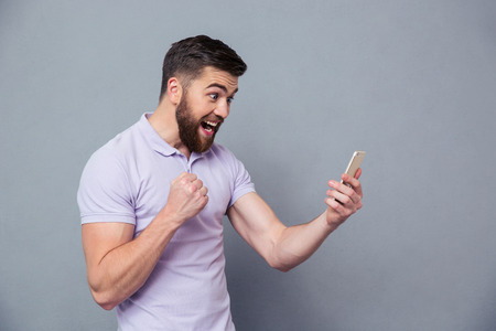Portrait of a cheerful man using smartphone over gray background