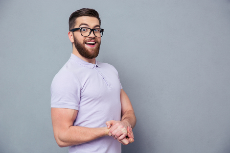 Portrait of a laughing casual man in glasses standing over gray background and looking at cameraの写真素材