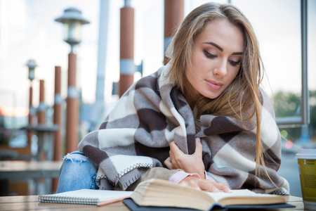 Portrait of attractive young woman reading book in cafe