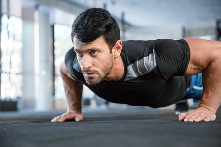 Foto de Portrait of a fitness man doing push ups in gym - Imagen libre de derechos