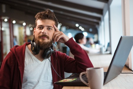 Photo pour Young handsome confident guy in brown hoodie working in office using headset and laptop - image libre de droit