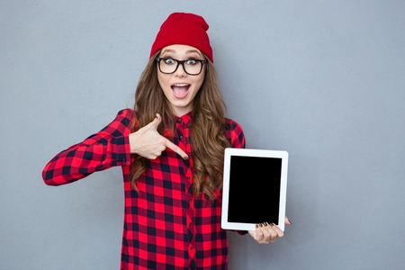 Photo pour Portrait of a cheerful hipster woman pointing finger on tablet computer screen over gray background - image libre de droit