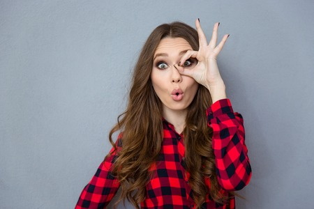 Funny amusing curly girl in checkered shirt showing okay gesture near her eyeの写真素材