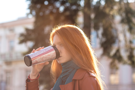 Beautiful redhead young lady with long hair in leather jacket and scarf drinking coffee from tumbler