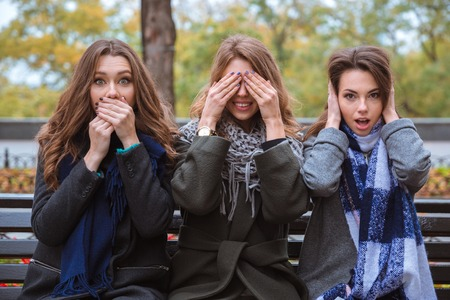 Photo pour Portrait of a three women sitting on the bench and representing senses: mute, blind and deaf outdoors - image libre de droit