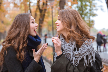Portrait of a two laughing women talking outdoors in autumn park