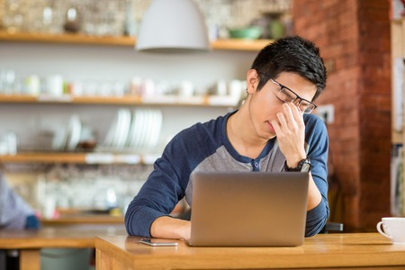 Tired exhausted young asian male working with laptop in cafe