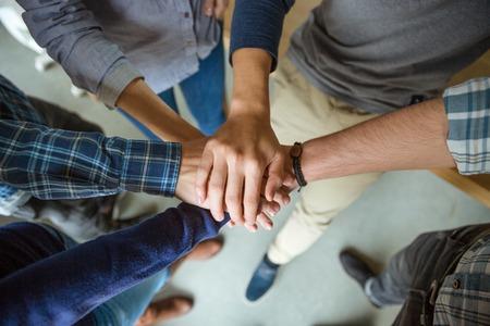 Foto de Top view of people joining hands together as a symbol of partnership - Imagen libre de derechos