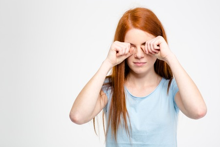 Sleepy tired young woman with long red hair rubbing her eyes by hands isolated over white background