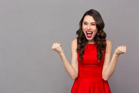 Photo pour Portrait of a cheerful woman in red dress celebrating her success over gray background - image libre de droit