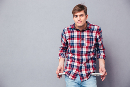 Photo for Poor handsome young man in checkered shirt and jeans showing empty pockets over grey background - Royalty Free Image
