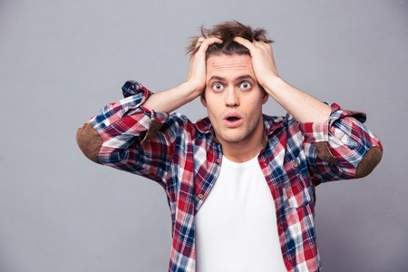 Photo pour Shocked dazed young man in plaid shirt holding head with both hands over grey background - image libre de droit