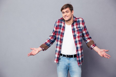 Confused cute young man in plaid shirt and jeans standing and shrugging over grey background