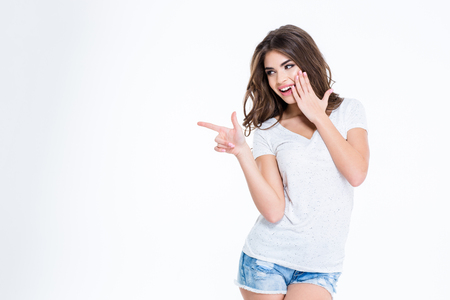 Photo pour Portrait of a young happy woman pointing finger away isolated on a white background - image libre de droit