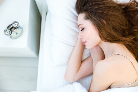 Photo pour Portrait of a young woman sleeping on the bed at home - image libre de droit