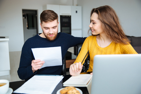 Photo pour Happy young couple calculating bills at home - image libre de droit
